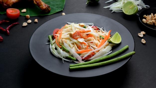Colpo potato dell'insalata della papaia, della griglia del pollo e degli ingredienti sulla banda nera