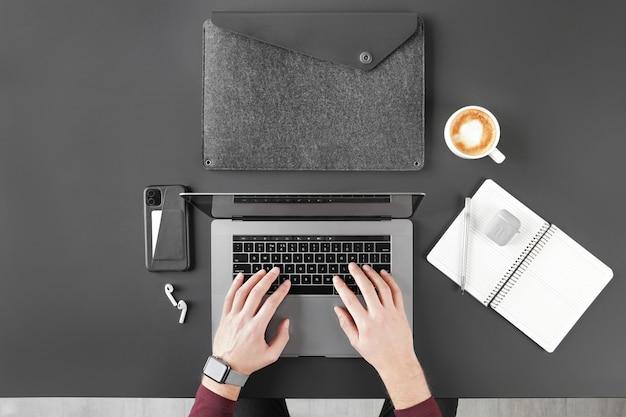 Colpo potato dell'uomo che lavora con il computer portatile sul piano d'appoggio nero con caffè e dispositivi digitali