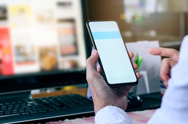 Colpo potato dell'uomo che per mezzo dello smartphone mentre lavorando alla scrivania, schermo in bianco per progettazione grafica.