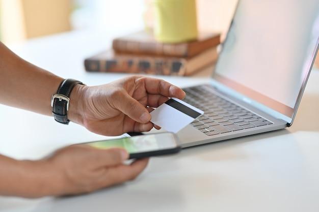 Colpo potato dell'uomo che utilizza il telefono cellulare e la carta di credito per il pagamento online.