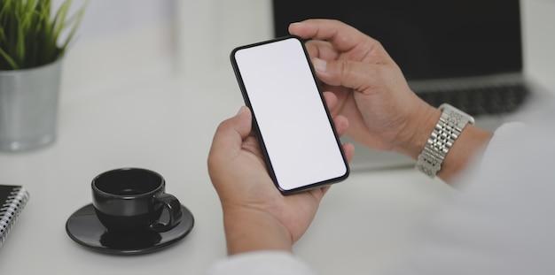Colpo potato dell'uomo d'affari che cerca informazioni sullo smartphone dello schermo in bianco