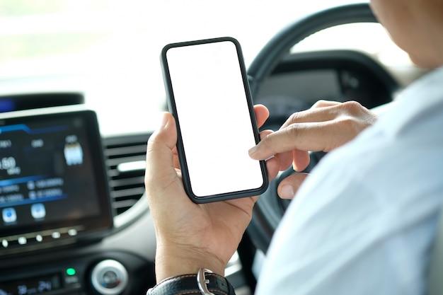 Colpo potato dell'uomo d'affari che tiene il telefono cellulare dello schermo in bianco in automobile.