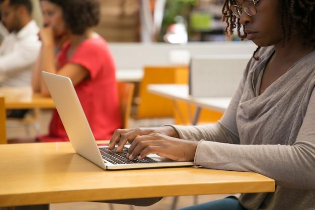 Colpo potato della donna premurosa che lavora con il computer portatile alla biblioteca