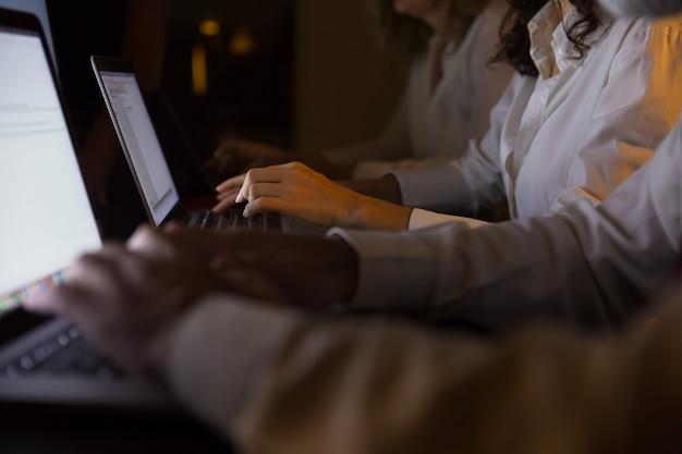 Colpo potato della gente di affari che lavora con i computer portatili