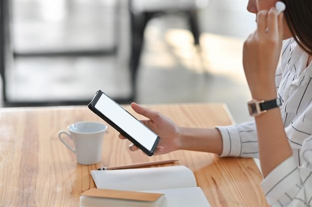 Colpo potato della giovane donna mentre usando l'auricolare e guardi il suo smartphone bianco dello schermo in bianco.