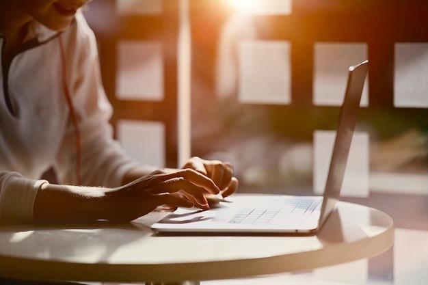 Colpo potato della mano femminile che scrive sul suo posto di lavoro del computer portatile a casa dello studio