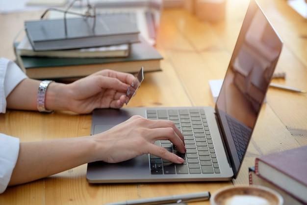 Colpo potato della mano femminile che tiene la carta di credito di plastica e che per mezzo del computer portatile. concetto di pagamento dello shopping online.
