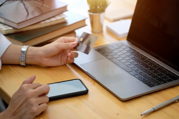 Colpo potato della mano femminile che tiene la carta di credito di plastica e che per mezzo dello smart phone allo scrittorio in ufficio. concetto di pagamento dello shopping online.
