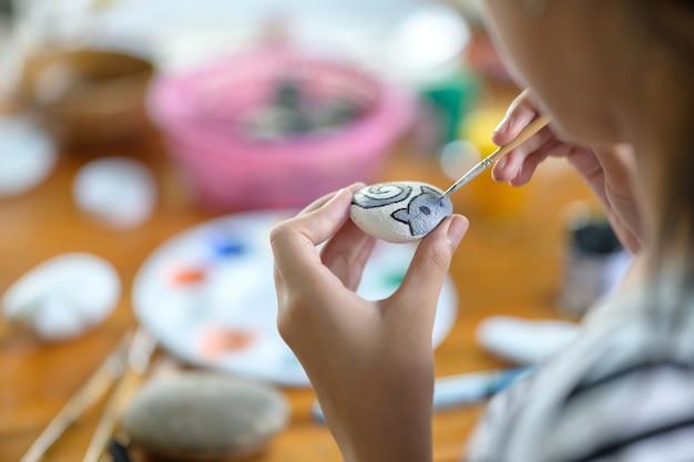 Colpo potato della pittura dell'artista della ragazza con colore di acqua su roccia.