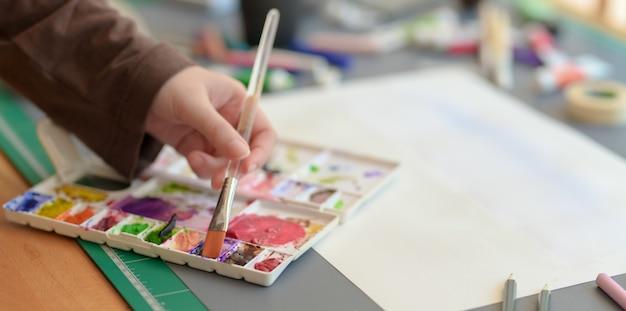 Colpo potato della pittura femminile dell'artista sul suo progetto con i colori di acqua