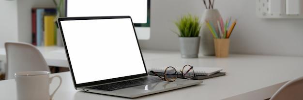 Colpo potato della scrivania minima con i dispositivi, gli articoli per ufficio e le decorazioni di computer dello schermo in bianco