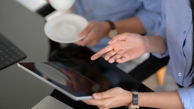 Colpo potato delle persone di affari che si consultano sul loro progetto con la compressa digitale