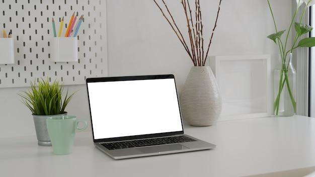 Colpo potato di area di lavoro minima con il computer portatile dello schermo in bianco, la tazza di caffè e le decorazioni
