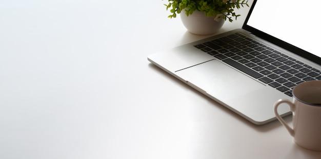 Colpo potato di area di lavoro minima con il computer portatile e il vaso dell'albero sulla tavola bianca della tavola