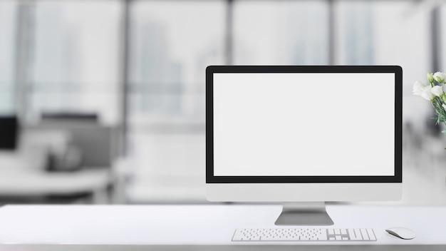 Colpo potato di area di lavoro semplice con il computer dello schermo in bianco sulla tavola bianca con il fondo vago della stanza dell'ufficio