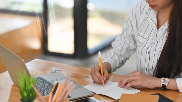 Colpo potato di giovane donna di affari mentre prendendo le note sullo scrittorio funzionante di legno nel posto di lavoro.
