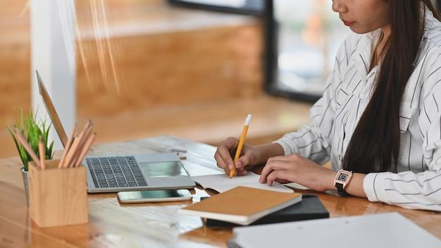 Colpo potato di giovane donna di affari mentre scrivendo un rapporto sullo scrittorio funzionante di legno.