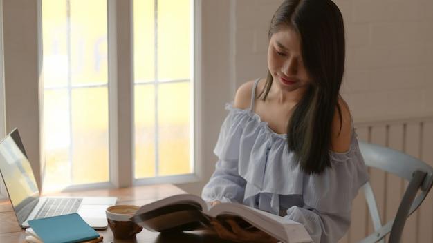 Colpo potato di un libro di lettura della ragazza mentre collocando accanto alla finestra nella stanza comoda