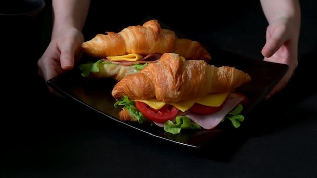 Colpo potato di un piatto del pasto della prima colazione con il prosciutto e il formaggio freschi del panino del croissant