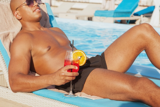 Colpo potato di un uomo africano muscolare che si rilassa vicino alla piscina, tenendo cocktail, spazio della copia. uomo rilassato che gode del suo drink a bordo piscina