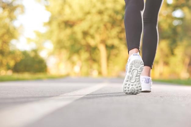 Colpo potato retrovisore di una donna di forma fisica che cammina nella foresta che riposa dopo la natura attiva pareggiante degli abiti sportivi di atletica di stile di vita del copyspace che esercita concetto.
