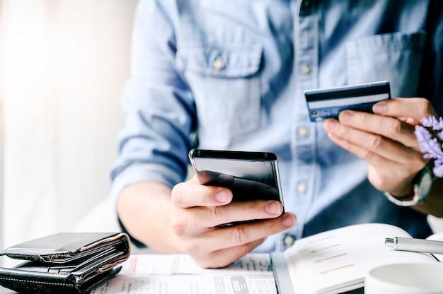 Colpo potato uomo pagando con carta di credito su smart phone a casa ufficio.