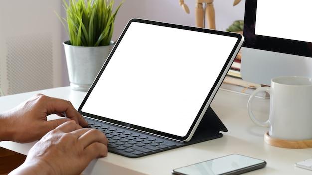 Colpo ritagliata della mano dell'uomo utilizzando tablet, smart keyboard, matita sull'area di lavoro