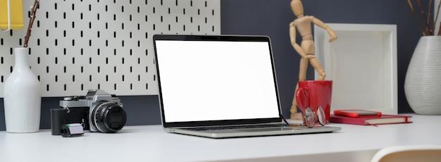 Colpo ritagliato di elegante home office desk con laptop, decorazioni e articoli per ufficio mock-up