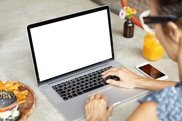 Colpo ritagliato di successo imprenditrice femminile in vacanza utilizzando il computer portatile, controllo e-mail, amici di messaggistica online, seduto al caffè con il taccuino aperto