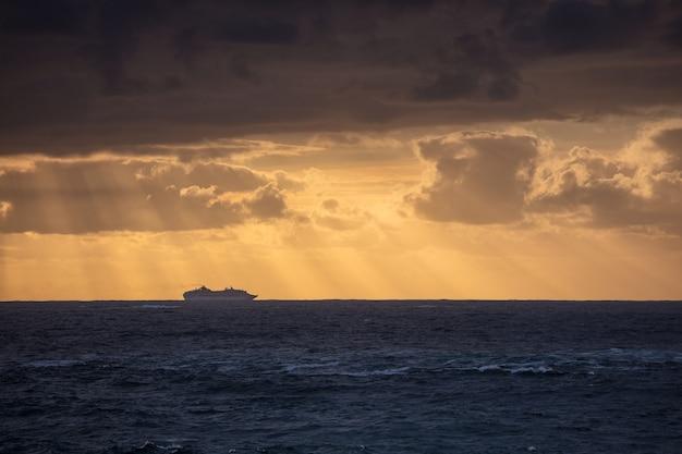 Colpo sbalorditivo dell'oceano blu calmo e della sagoma di una nave sotto un cielo nuvoloso durante il tramonto