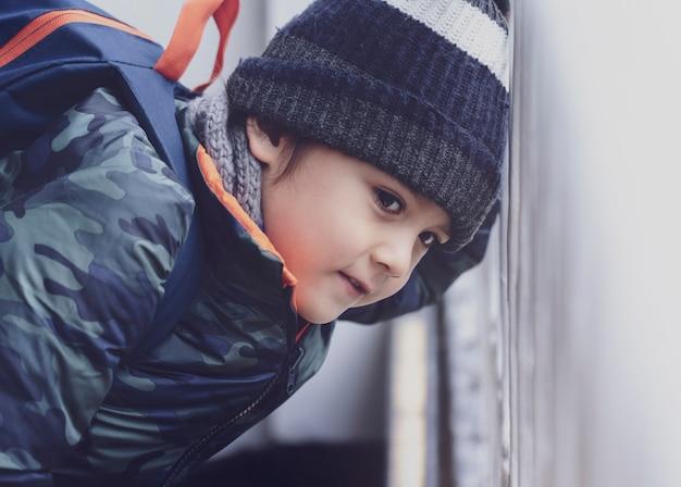 Colpo schietto del ragazzino che osserva attraverso il fench di metallo sulla strada, scatto ritagliato del bambino zaino con calda avventura di panno invernale in città, vista laterale ritratto bambino guardando fuori con la faccia sorridente