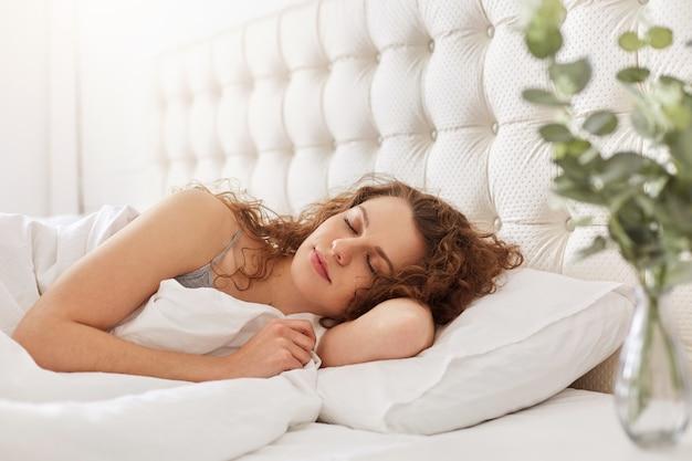 Colpo schietto di giovane donna compiaciuta si gode un buon sonno in camera da letto, si trova in un letto comodo, ha un aspetto accattivante, tiene gli occhi chiusi, giace sotto le lenzuola bianche. la bella femmina ha riposo.
