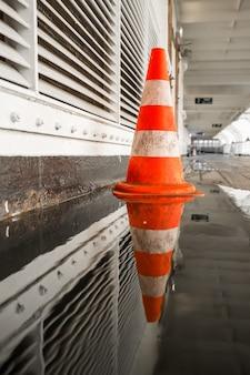 Colpo selettivo di un cono di traffico arancione sul lato del corridoio con una pozzanghera che lo riflette