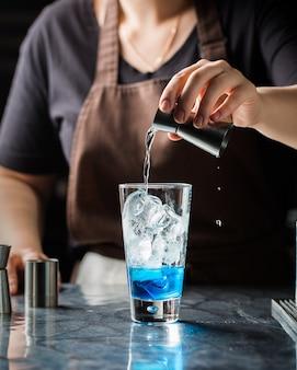 Colpo selettivo verticale del primo piano di una femmina che produce bevanda alcolica blu con ghiaccio