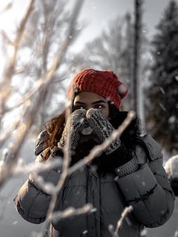 Colpo selettivo verticale di una femmina che indossa cappello rosso, guanti e giacca grigia durante l'inverno