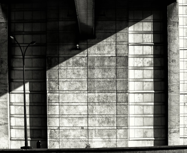 Colpo simmetrico di gradazione di grigio di una parete ombreggiata pietra - depressione, concetto di solitudine