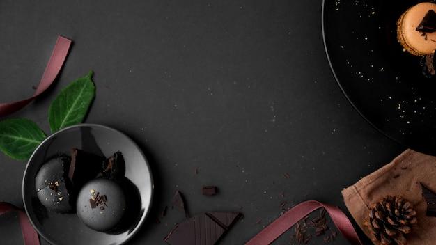 Colpo sopraelevato dei macarons del cioccolato fondente sulla banda nera sulla tavola scura