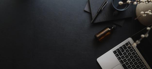 Colpo sopraelevato del computer portatile moderno scuro di spirito dell'area di lavoro e dello spazio della copia con gli articoli per ufficio