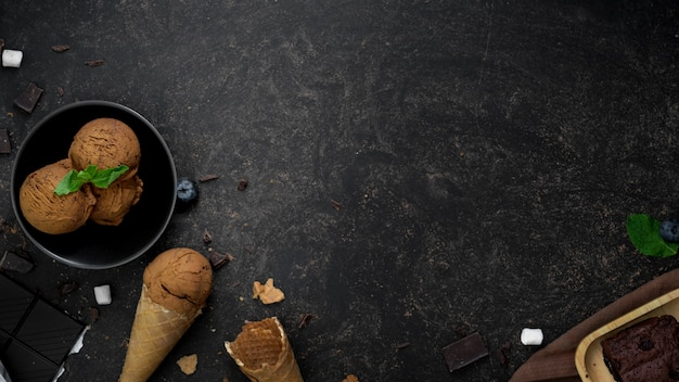 Colpo sopraelevato del dessert di estate con i coni di gelato di sapore del cioccolato sulla tavola scura