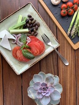 Colpo sopraelevato del primo piano di un'insalata con i fagioli e il formaggio su un piatto quadrato con una forcella
