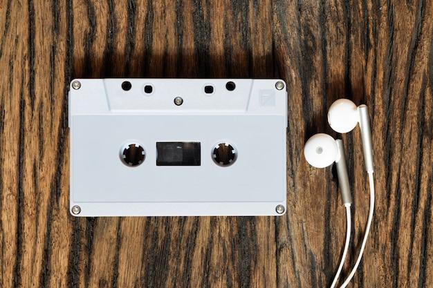 Colpo sopraelevato di retro vecchio nastro a cassetta audio con il trasduttore auricolare sul fondo di legno d'annata di lerciume, vista superiore