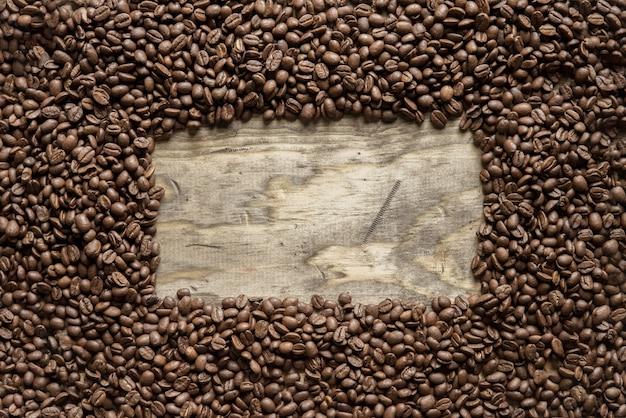 Colpo sopraelevato di una struttura dei chicchi di caffè sopra una superficie di legno grande per fondo o testo di scrittura