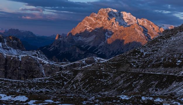 Colpo strabiliante di un paesaggio nelle alpi italiane sotto il cielo nuvoloso di tramonto