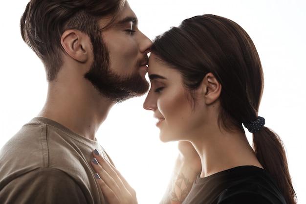 Colpo tenero dell'uomo bello che bacia donna alla fronte.