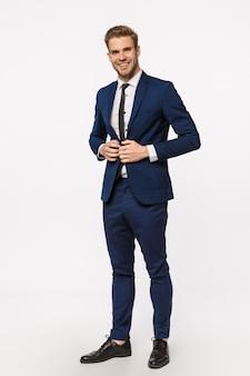 Colpo verticale, a figura intera bel giovane uomo d'affari di successo e ricco in giacca e cravatta, allaccia i bottoni sulla giacca, sorride assertivo, si sente sicuro e fortunato, determinato caso di vittoria in tribunale