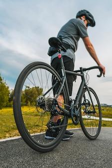 Colpo verticale del ciclista con una bici da strada sulla pista ciclabile.