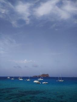 Colpo verticale del mare con diverse barche galleggianti vicino a ibiza, spagna