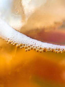 Colpo verticale del primo piano di birra in un vetro - perfetto per un fresco