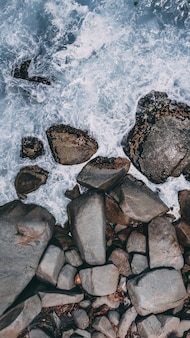 Colpo verticale dell'angolo alto di grandi pietre nell'acqua tempestosa dell'oceano