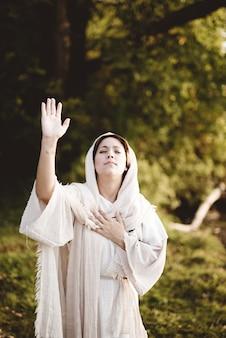 Colpo verticale della femmina che indossa un abito biblico con le mani in alto verso il cielo pregando